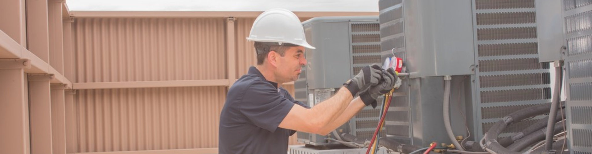 Technician taking a cover plate off an air conditioner condenser