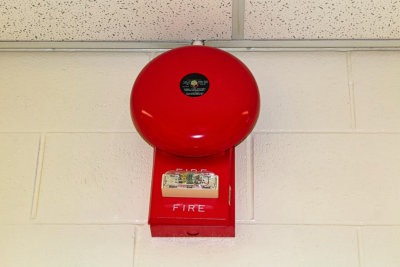 red fire alarm hanging on a white brick wall