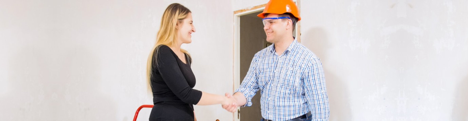 young businesswoman shaking hands with contractor at house under renovation