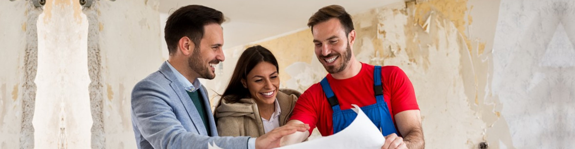couple looking blueprints of their home with builder handyman